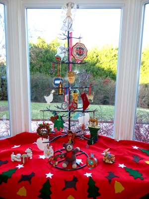 everlasting tree with ornaments that hold meaning and a handmade felt tree skirt repurposed in the bay window