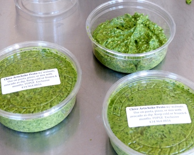 finished pesto divied up into 8 OZ deli containers, ready for chill down, then freezer.