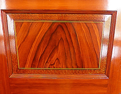 "pine doors are given their inlaid mahogany appearance by a painting process called ""graining."" This was a very popular technique used during the 19th century. Inexpensive, local woods could be used, sidestepping the costs of imported versions."