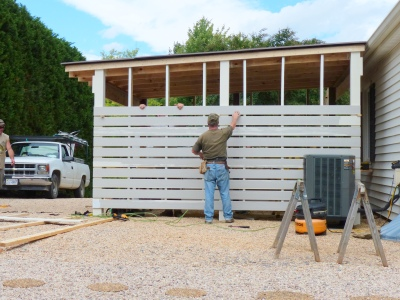 MiraTEC slats applied to posts and framing, one inch apart. These guys made building look easy...