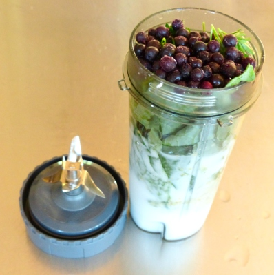 the cup is full of greens and topped with blueberries and other fruits of choice